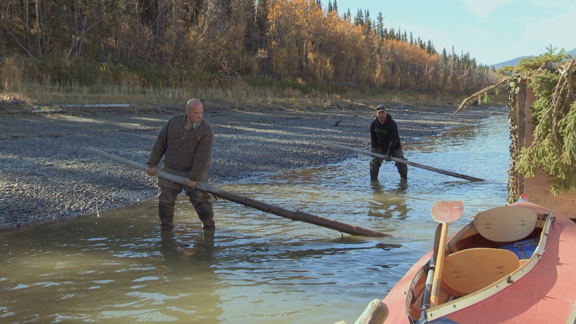 YUKON RIVER, Alaska - Lance Kramer and Charles Keeter prying their raft free. (Photo Credit: National Geographic Channels/Eric Babisch)