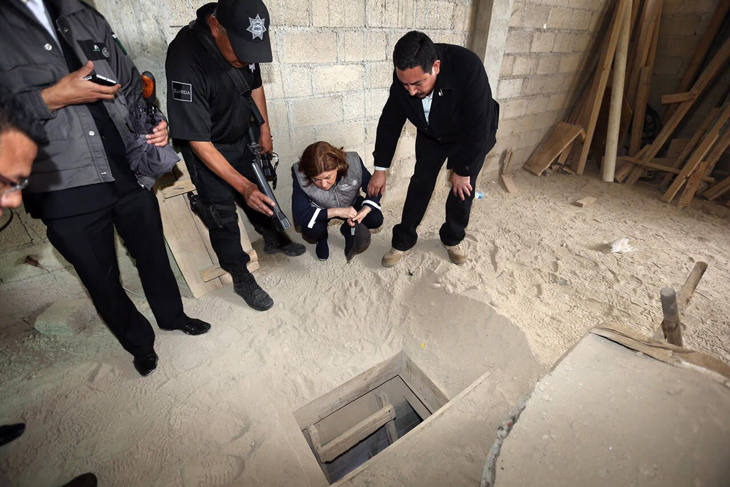 "In this photo provided by Mexico's attorney general, authorities inspect the exit of the tunnel they claim was used by drug lord Joaquin ""El Chapo"" Guzman to break out of the Altiplano maximum security prison in Almoloya, west of Mexico City, Sunday, July 12, 2015. A massive manhunt is underway after Guzman, escaped from the maximum security prison through the tunnel that opened into the shower area of his cell, the country's top security official announced. (Mexico's Attorney General's Office via AP)"